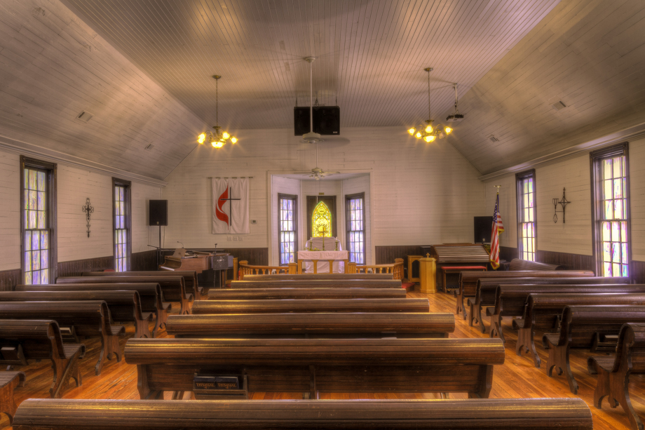 Wooden pews, heart pine floors and colored window panes are among the interior features of Fields Chapel United Methodist Church. Photo by Scott MacInnis, courtesy Historic Rural Churches of Georgia.