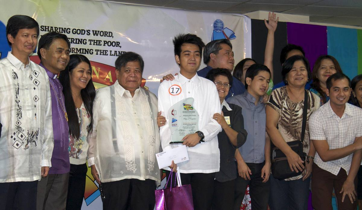 Alexis John Caguingin holds his trophy after winning the senior division of the National Bible Quiz held in Manila, Philippines.