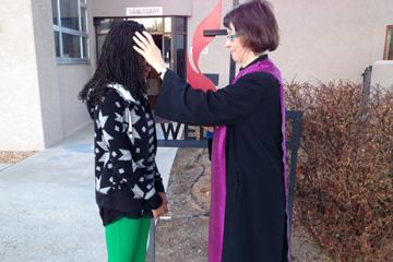 La Rda. Kim Kinsey ofrece cenizas a una joven en la acera exterior de la Iglesia Metodista Unida Cristo en Albuquerque, Nuevo México. Foto cortesía de la Rvda. Kim Kinsey.