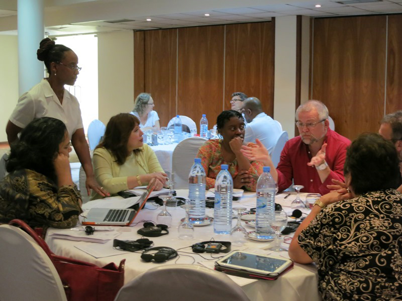 Connectional Table members spoke in small groups about different legislative approaches to the denomination's sexuality debate during their meeting in Maputo, Mozambique. Pictured from far left are Monalisa Tuitahi, the Rev. Kennetha Bigham-Tsai (standing), Bishop Minerva Carcaño, the Rev. Tamara Brown, the Rev. Ole Birch, the Rev. Harald Rückert and Josephine Deere. Photo by Heather Hahn, UMNS