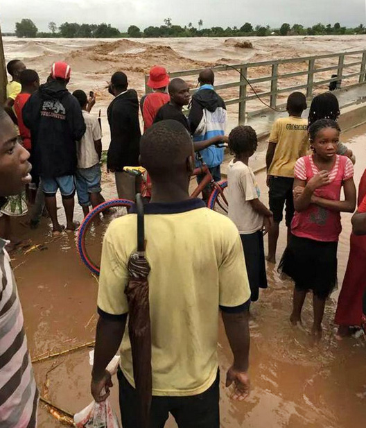 People in watch as flood waters rise dangerously high in Mozambique.  Photo by Quari Ziyaad Patel
