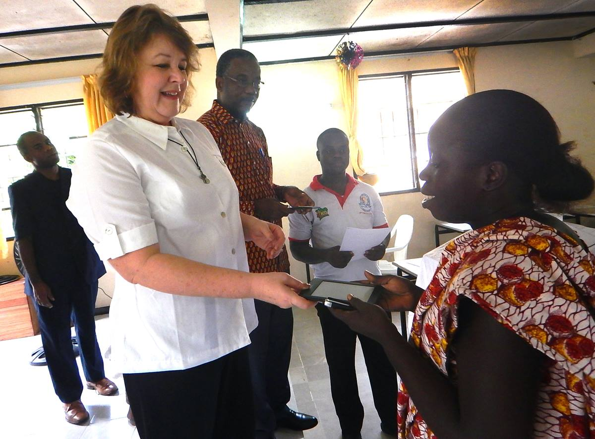 Christelle Mambo (right) receives an e-reader from Robin Pippin at the United Methodist seminary in Abadjin-Doumé, Côte d'Ivoire