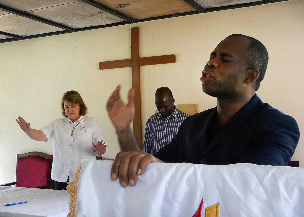 Instructors Robin Pippin (left) and the Rev. Adriano Quelende raise their hands in prayer at the United Methodist seminary in Abadjin-Doumé, Côte d'Ivoire on Feb 9., the date that the students signed their agreements and received e-readers.