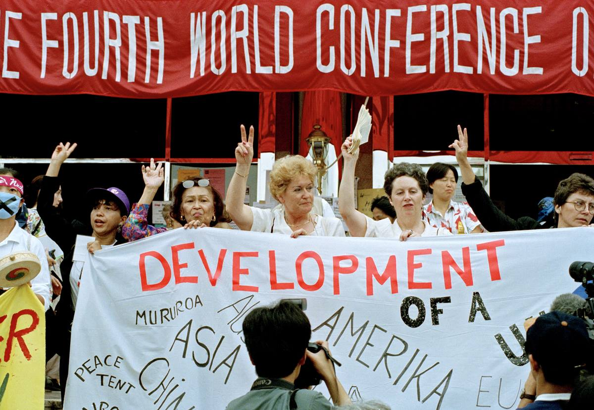Participants carry a sign during the forum for nongovernmental organizations in Huairou, China, part of the 1995 U.N. Fourth World Conference on Women. Photo by Milton Grant, U.N.