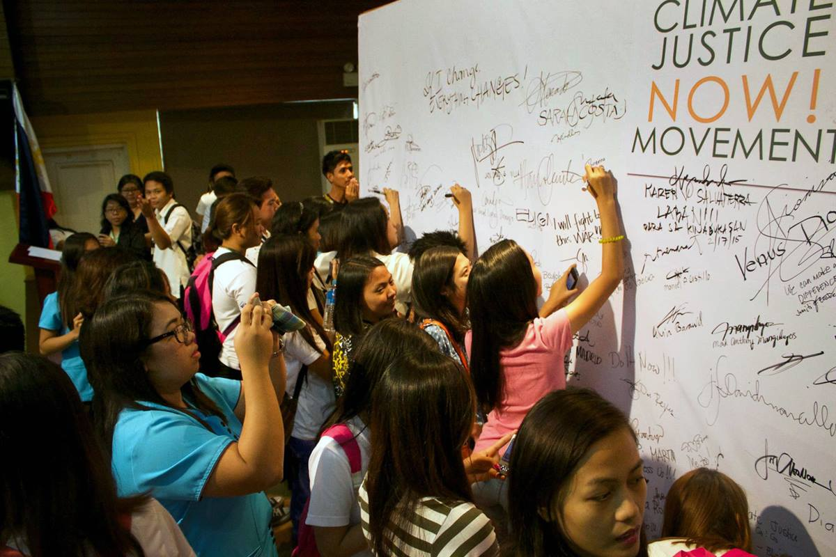 About 300 students, faculty, staff and guests join the Climate Justice Now! movement by signing their names during a forum held in Cabanatuan City at Wesleyan University-Philippines.  Photo by Gladys Mangiduyos