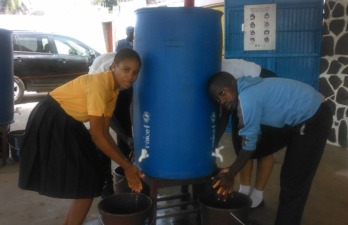 Students at J.J. Roberts United Methodist School in Liberia use one of the large hand-washing stations in this file photo from March 2015. School opened in March after being closed for months due to Ebola. File photo by Nyamah Dunbar, UMNS