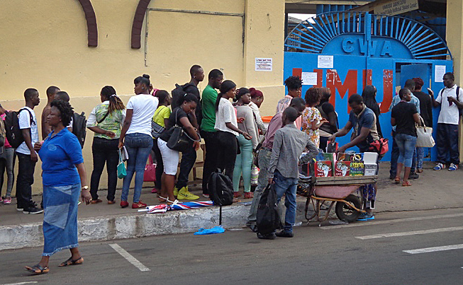 United Methodist University students line up before the school gates for a temperature check and hand- washing in Monrovia, Liberia. Those precautions are in place because of Ebola. Photo by Julu Swen, UMNS