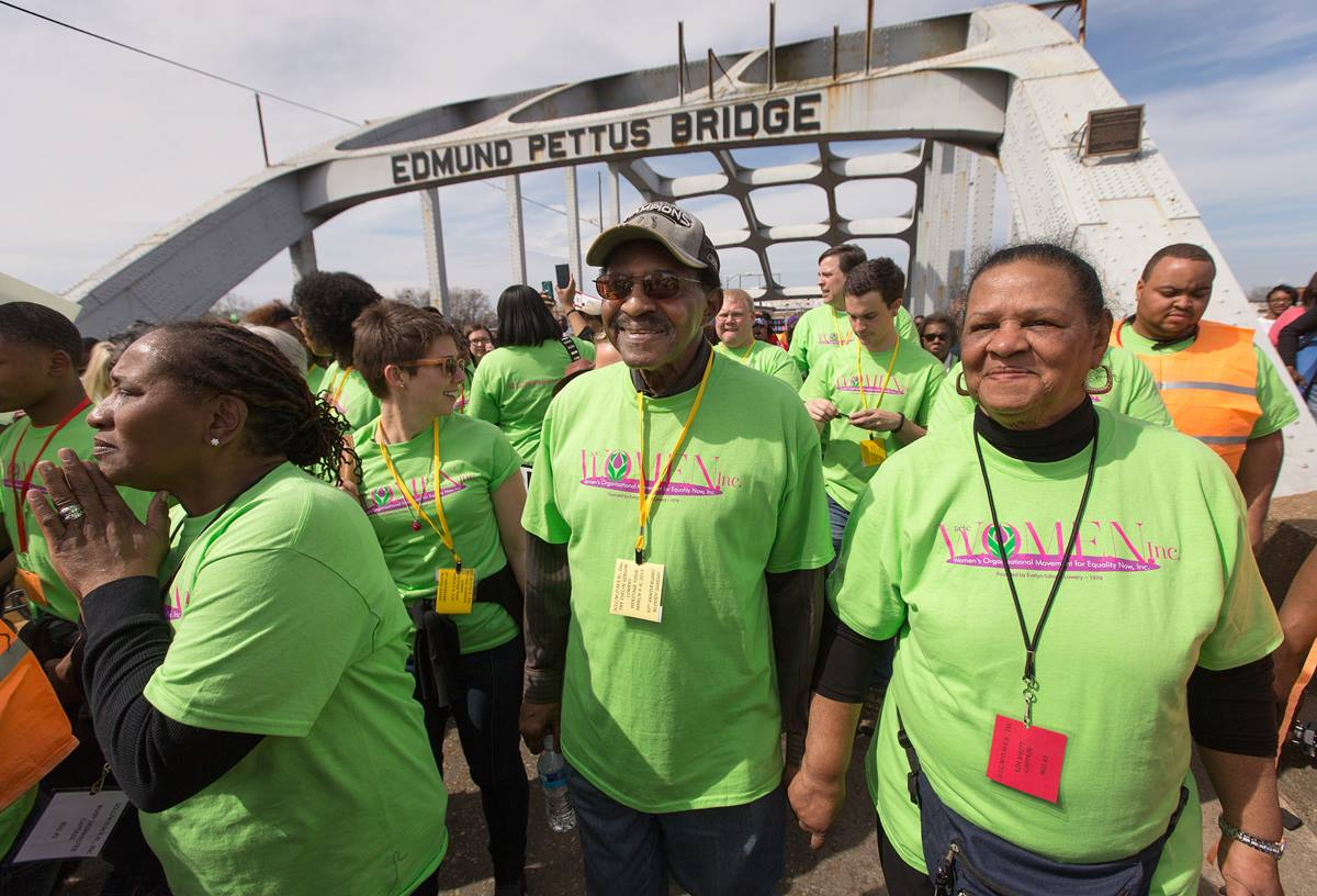 """United Methodist Bishop Woodie W. White (center) crosses the Edmund Pettus Bridge in Selma, Ala., during the 50th anniversary observance of the """"Bloody Sunday"""" civil rights march. He is joined by his wife Kim (right), Ruby Shinhoster of the Southern Christian Leadership Conference's Women's Organizational Movement for Equality Now (left) and Candler student Beth Clark.  Photo by Mike DuBose, UMNS"""