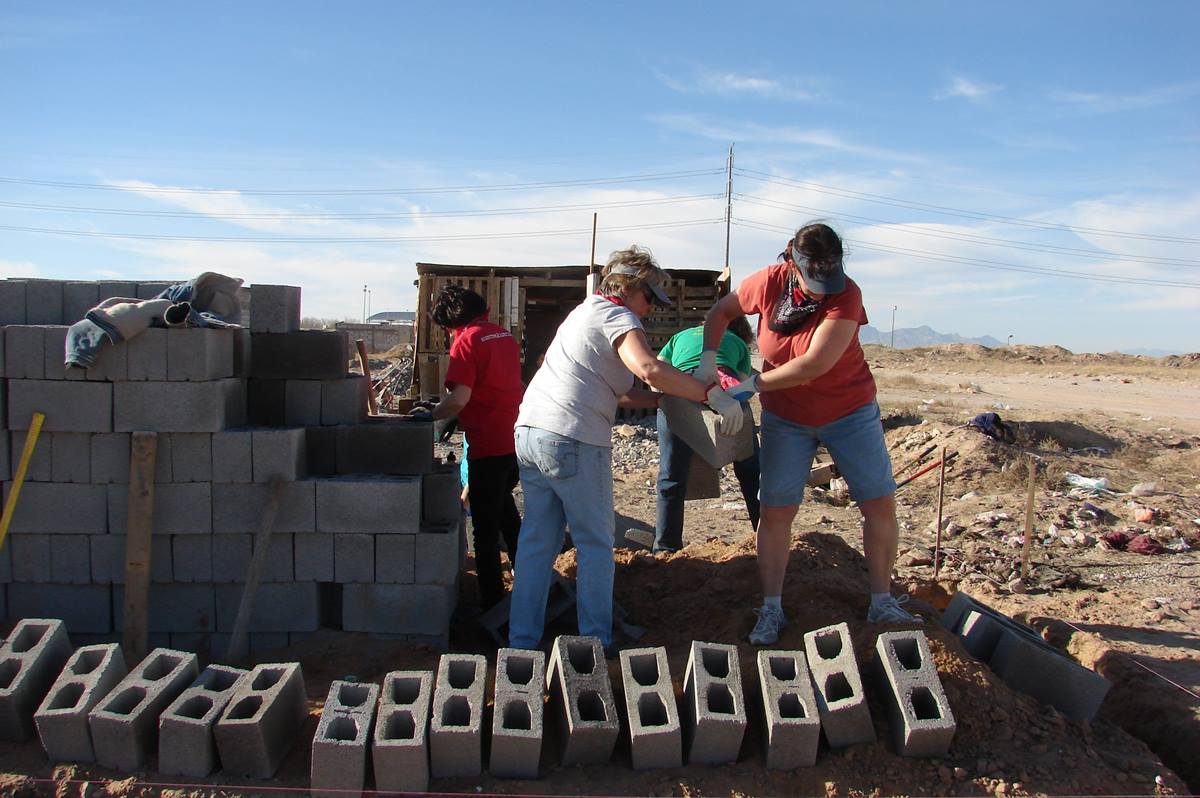 Dawn Moneyheffer (left) and Rita Thomas handle cinder blocks while helping the Suncreek United Methodist Church mission team build a home last month for a needy family in Ciudad Juárez, Mexico. Photo by Sam Hodges, UMNS
