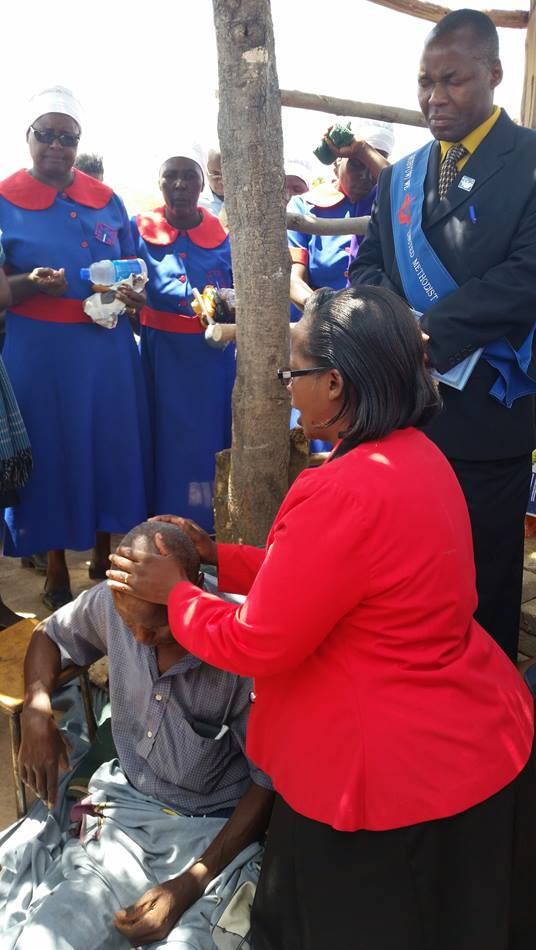 Pastor Rufaro Magomo prays for the healing of Marck Muringani who has been ill for four months.