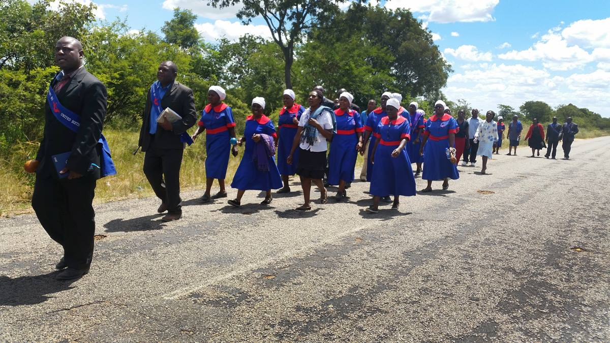 The United Methodist evangelism team from the Chitungwiza-Marondera district walk over 6km preaching and inviting residents during a three-day revival in Mahusekwa, Zimbabwe. In this photo, the team is enroute to their final stop, the Mahusekwa Government Hospital.