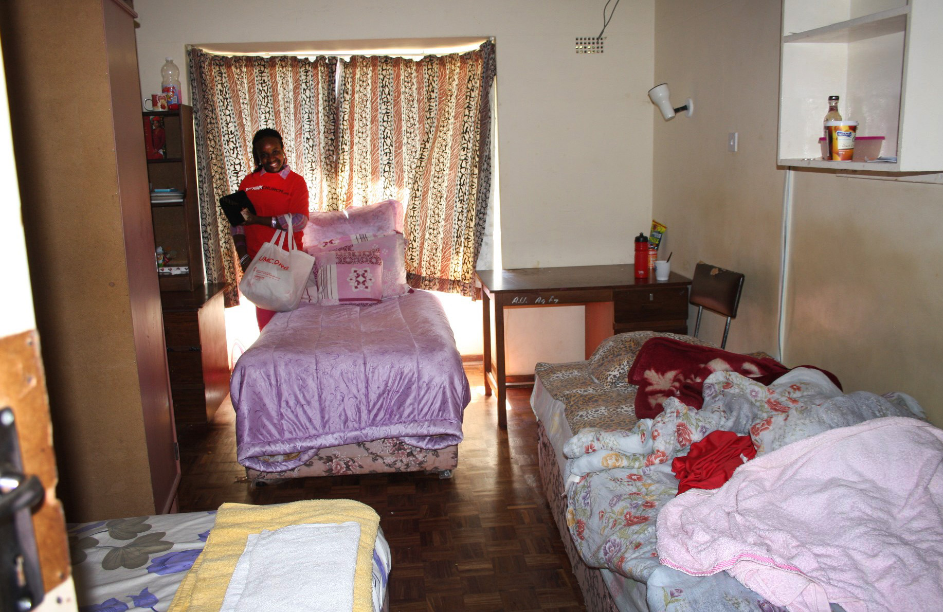 Three beds are visible in Tapiwawashe Muganyura's room in one of the women's residence halls at Africa University. The board of directors encouraged Vice Chancellor Munashe Furusa to come up with a plan to renovate the aging buildings and build new ones. Photo by Vicki Brown, UMNS