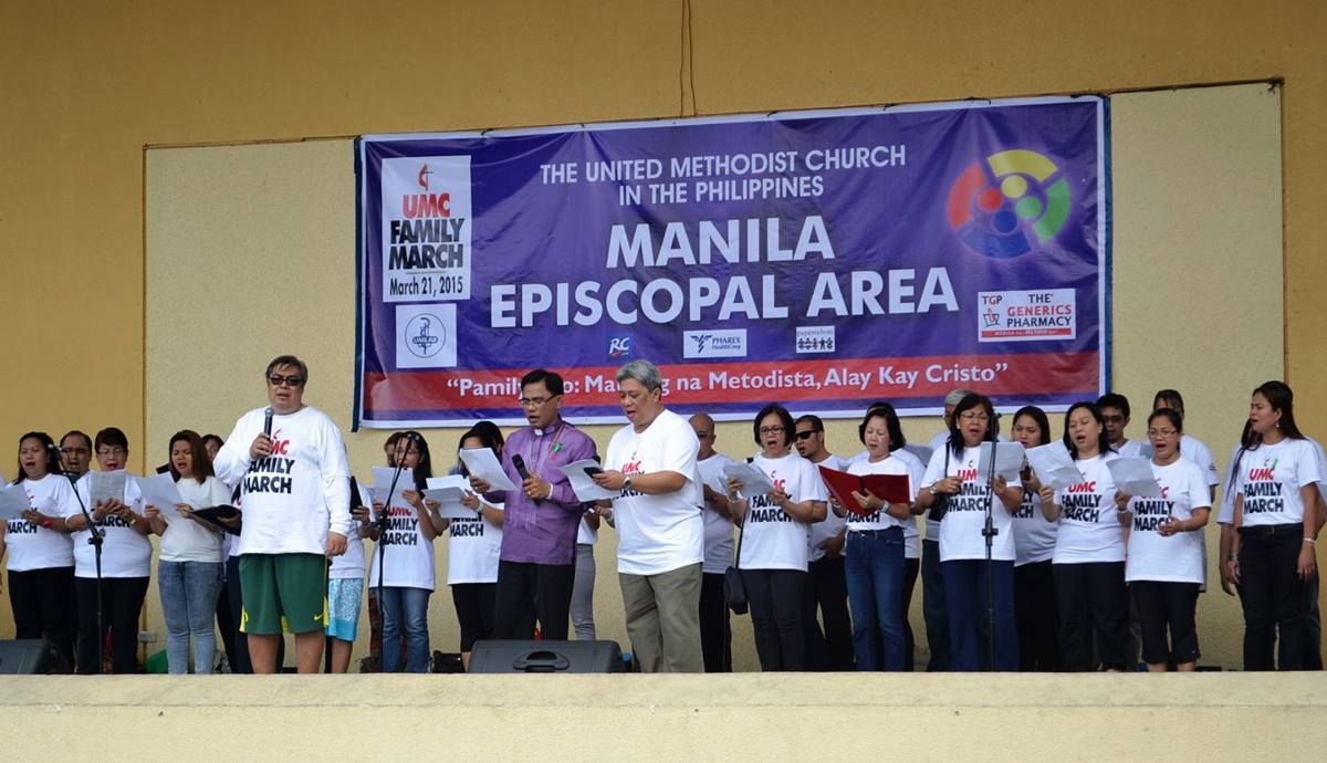 (From front left) Arnel de Pano, director of the unity choir, Bishop Rodolfo Juan, and the Rev. John Manalo lead the crowd during the United Methodist family march event in Quezon City, Philippines. Photo by SJ Earl Canlas and Jimuel Mari
