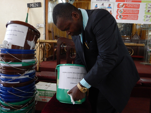 Leonard Ben Gbloh, Sierra Leone Annual conference's primary schools education secretary, demonstrates how to set up and use the hand washing buckets.