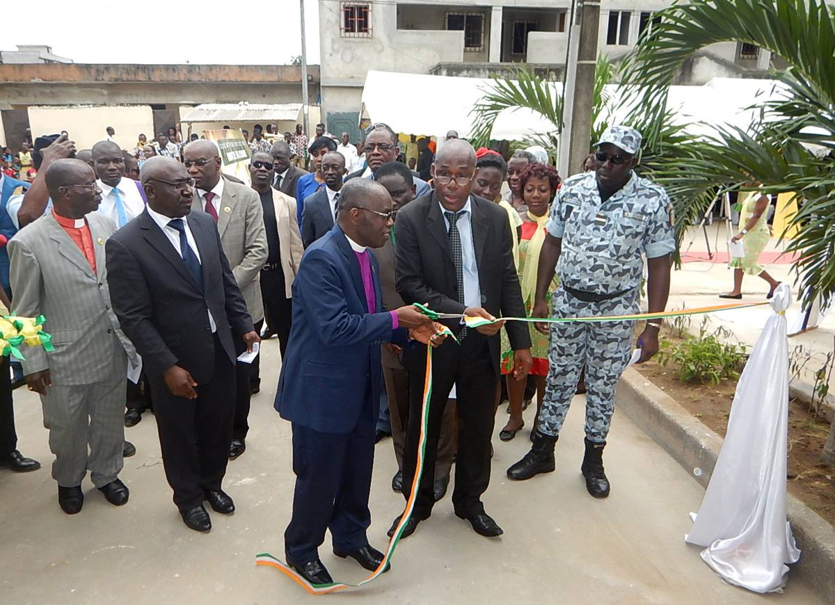 Bishop Benjamin Boni and Georges Yao Bi, a representative of the Ivorian Ministry of Tourism (right) cut the ribbon as part of the inauguration of the Côte d'Ivoire United Methodist Church missionary guest house. Photo by Isaac Broune, UMNS