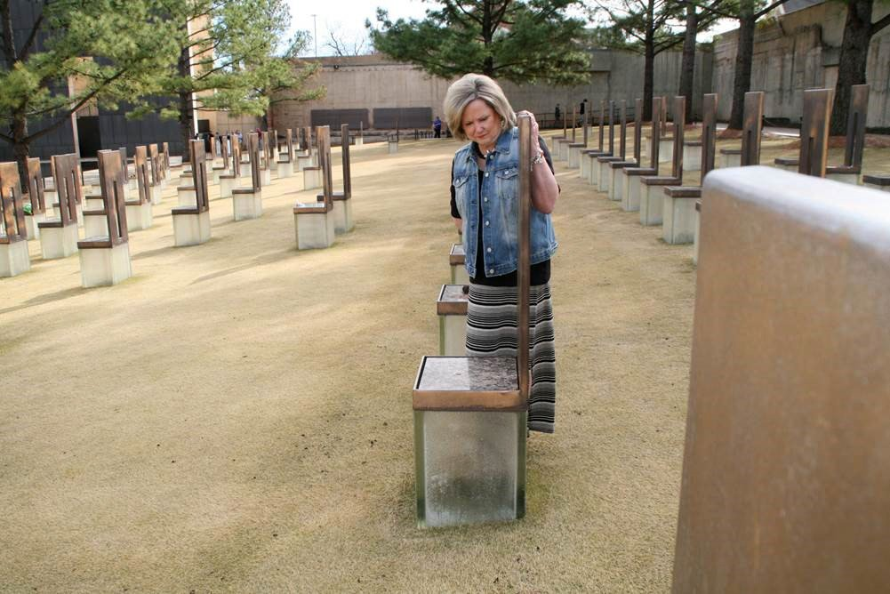 "The ""Field of Empty Chairs"" at the Oklahoma City National Memorial and Museum marks the footprint of the Alfred P. Murrah Federal Building. Each of the 168 translucent chairs represents a person killed in the bombing. Ruth Schwab stands at the chair that represents one of her best friends, Patricia Nix. Photo by Boyce A. Bowdon, UMNS"