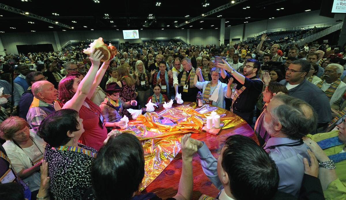 Dozens of demonstrators demanding a more inclusive church took over the floor of a May 3 session of the 2012 United Methodist General Conference in Tampa, Florida. They held communion around the center table and sang songs, causing the presiding bishop to suspend the morning session. Photo by Paul Jeffrey, UMNS
