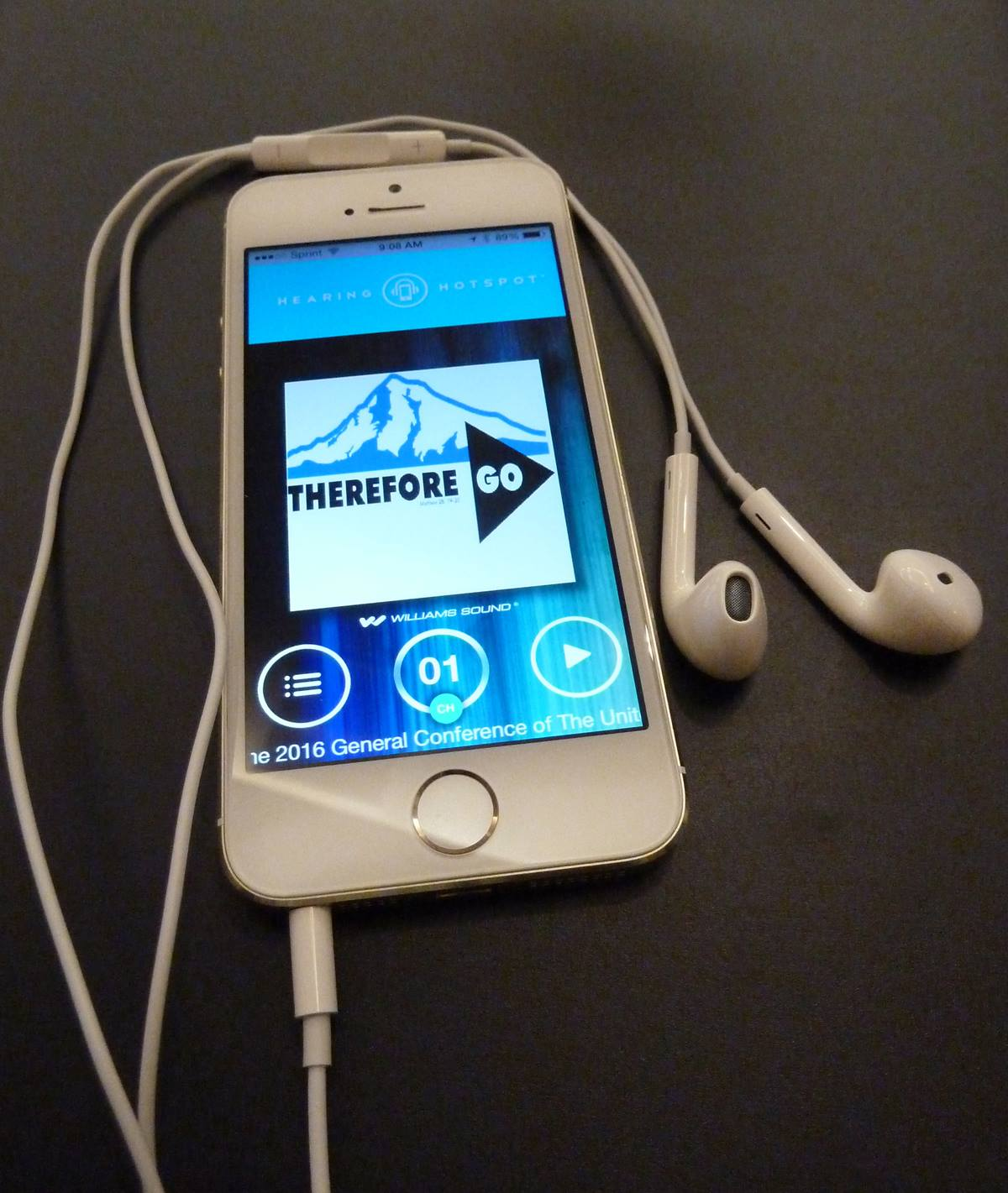 """A smart phone displays the logo """"Therefore Go"""" used for the United Methodist General Conference 2016. The headphones and app could provide a """"hearing hotspot"""" for translation into different languages.  Photo by Greg Nelson"""