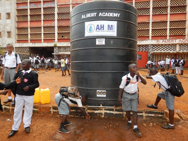 Students at the Albert Academy in Western Freetown wash hands at end of break time before going back to their classes. The Ministry of Health has provided huge water tanks in many schools which are regularly refilled so that staff and students can wash hands regularly during school hours.