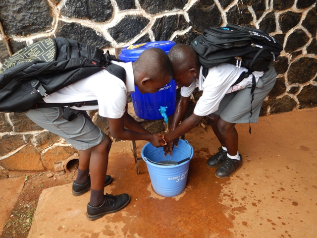 Students at the Albert Academy wash hands outside before they are allowed into their classroom. The students take hand washing seriously.