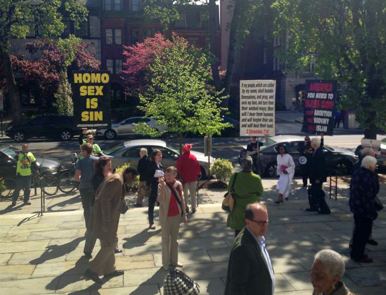 Protesters carry signs outside Foundry United Methodist Church on April 26.