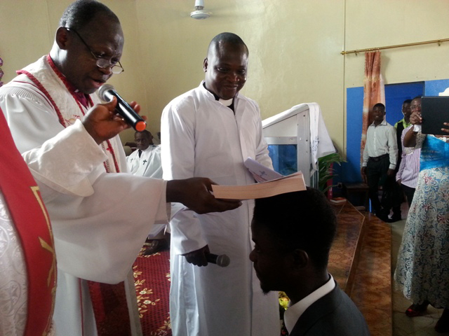 In this file photo, Bishop John K. Yambasu uses a Bible instead of laying on of hands during the induction of clergy as deacons and elders due to the Ebola outbreak. Senesie Rogers is being inducted as interim young adults president.
