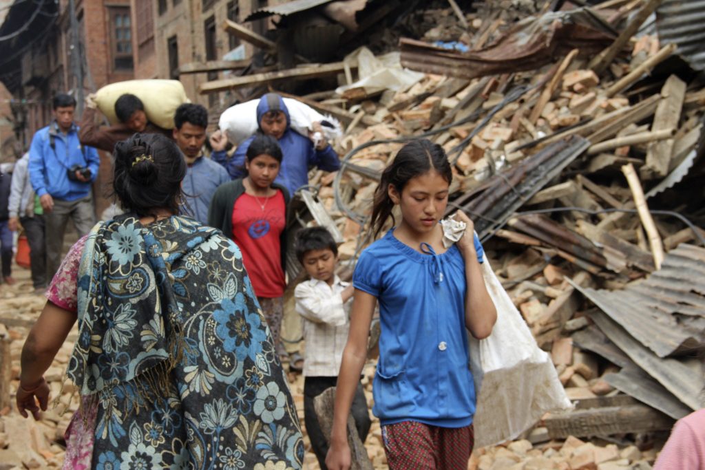 Earthquake survivors make their way past piles of rubble in Kathmandu, Nepal. Accessing affected rural villages remains a significant challenge, say United Methodist missionaries assigned there.