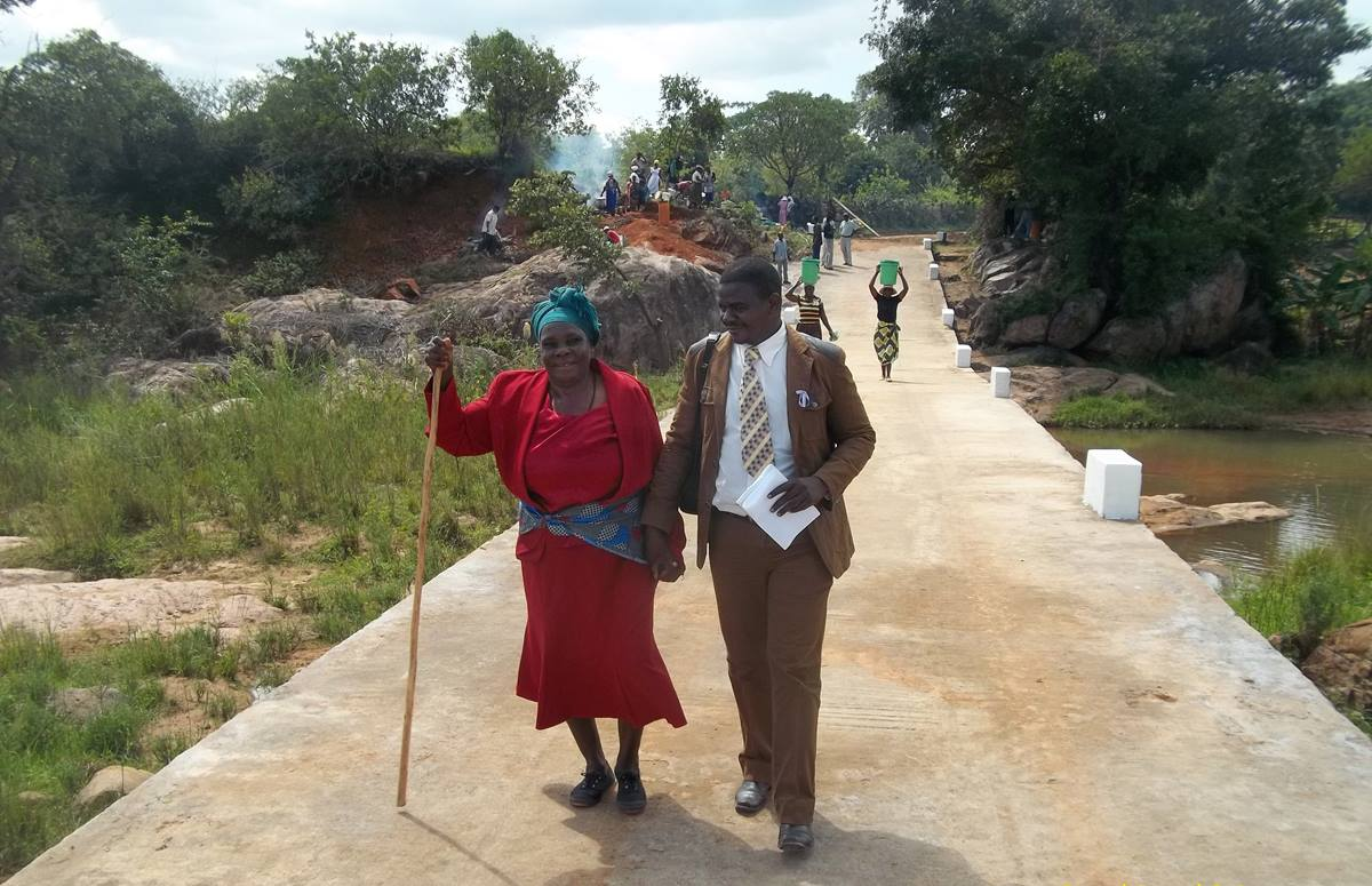 Taurai Emmanuel Maforo assists Keresia Muzaruwetu in crossing the new Chitora-Gwarada Bridge in Zimbabwe. Photo courtesy of Zimbabwe East Conference.