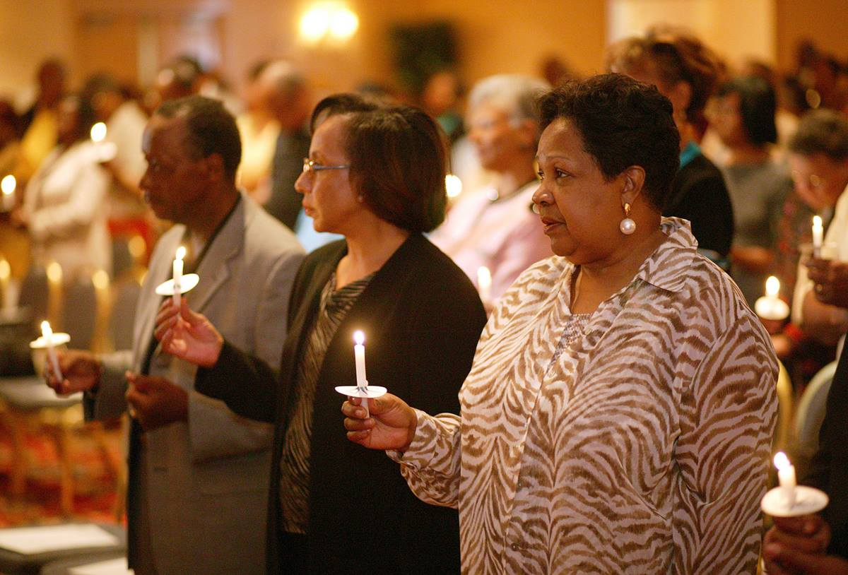 Participants in the first reunion of the former Central Jurisdiction light candles in memory of those who have gone before them. A UMNS photo by Mike DuBose.