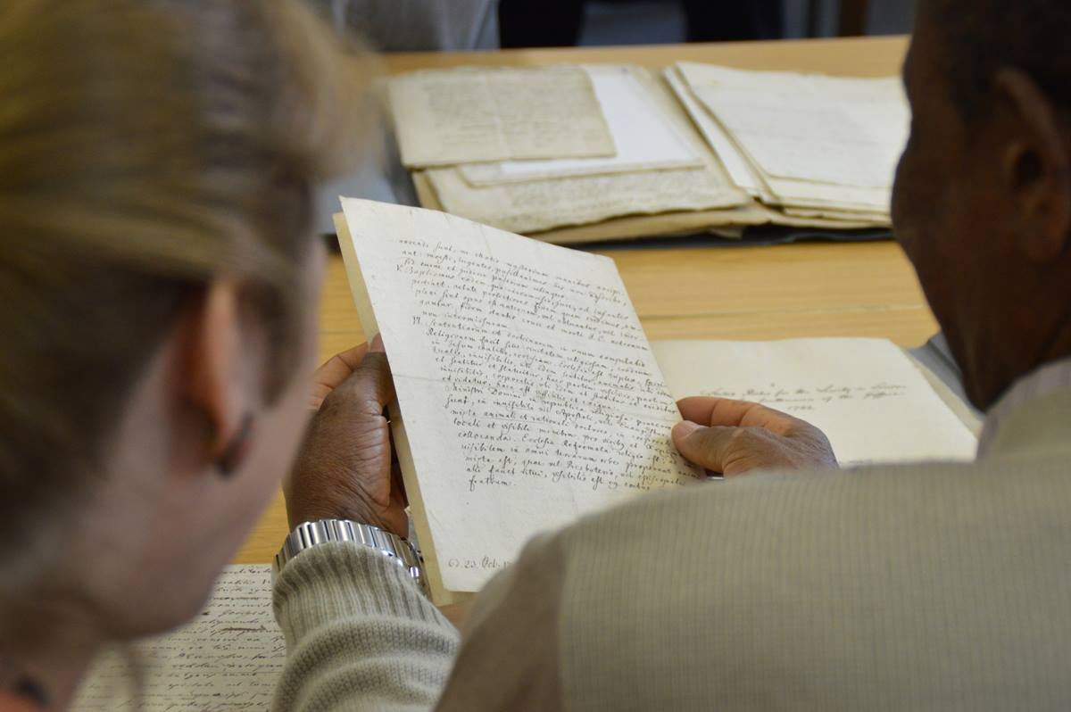 The Rev. Jean Hawxhurst and Zimbabwe Area Bishop Eben K. Nhiwatiwa examine letters exchanged by John Wesley and Count Nikolaus Ludwig von Zinzendorf. During a pilgrimage to Herrnhut, Germany, United Methodists visited the Moravian Church's archives. Photo by Klaus Ulrich Ruof