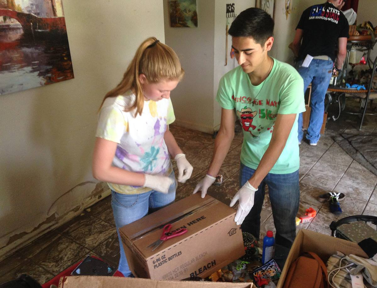 An online ministry of First United Methodist Church in San Marcos, Texas, helped recruit and organize volunteers to help with flood relief there. Students from San Marcos High School and Texas State University removed items from a flooded home in San Marcos' Blanco Garden area. Photo by the Rev. Todd Salmi