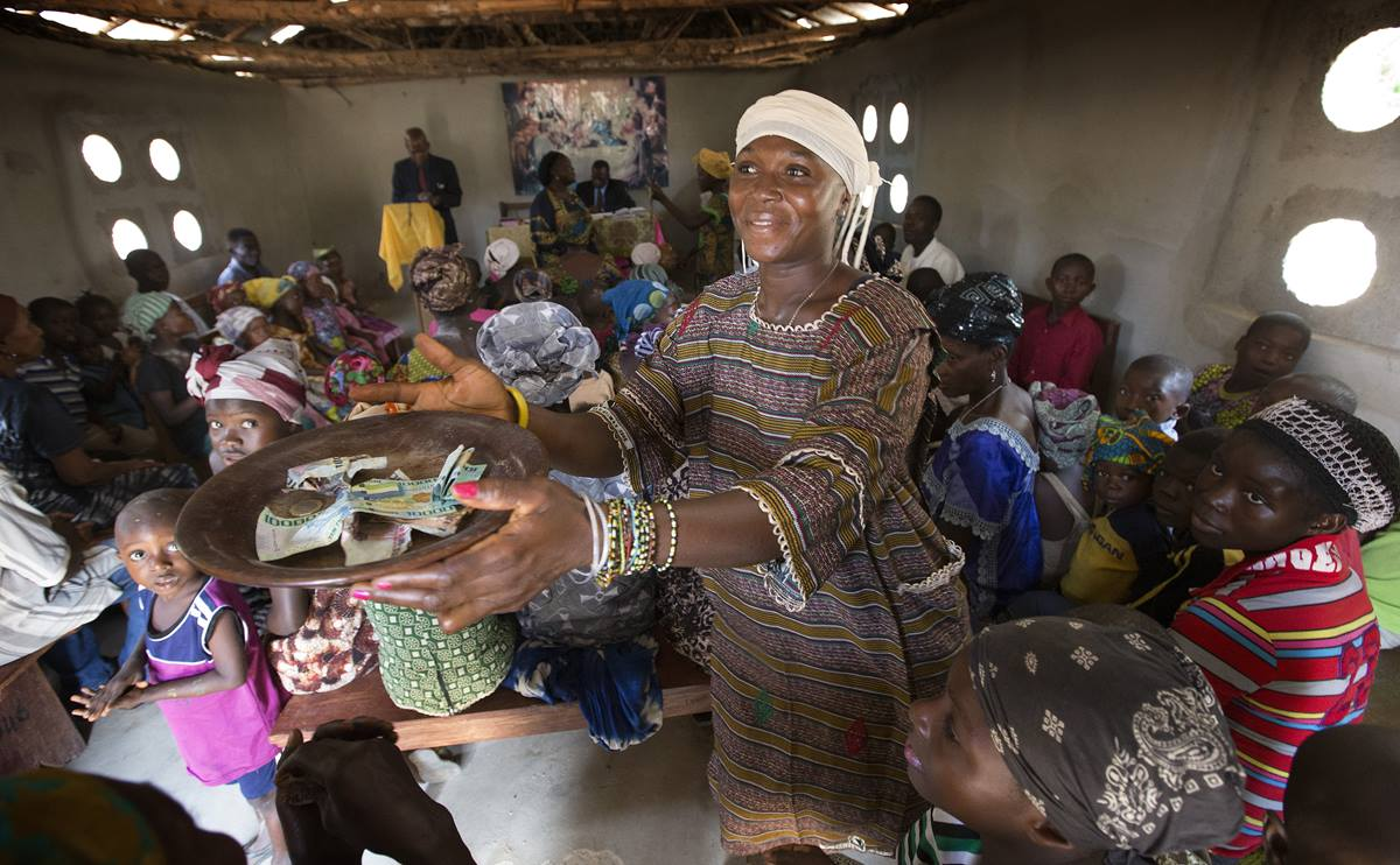 Zainab Koroma collects the offering at the United Methodist church in Fulawahun, near Bo, Sierra Leone.