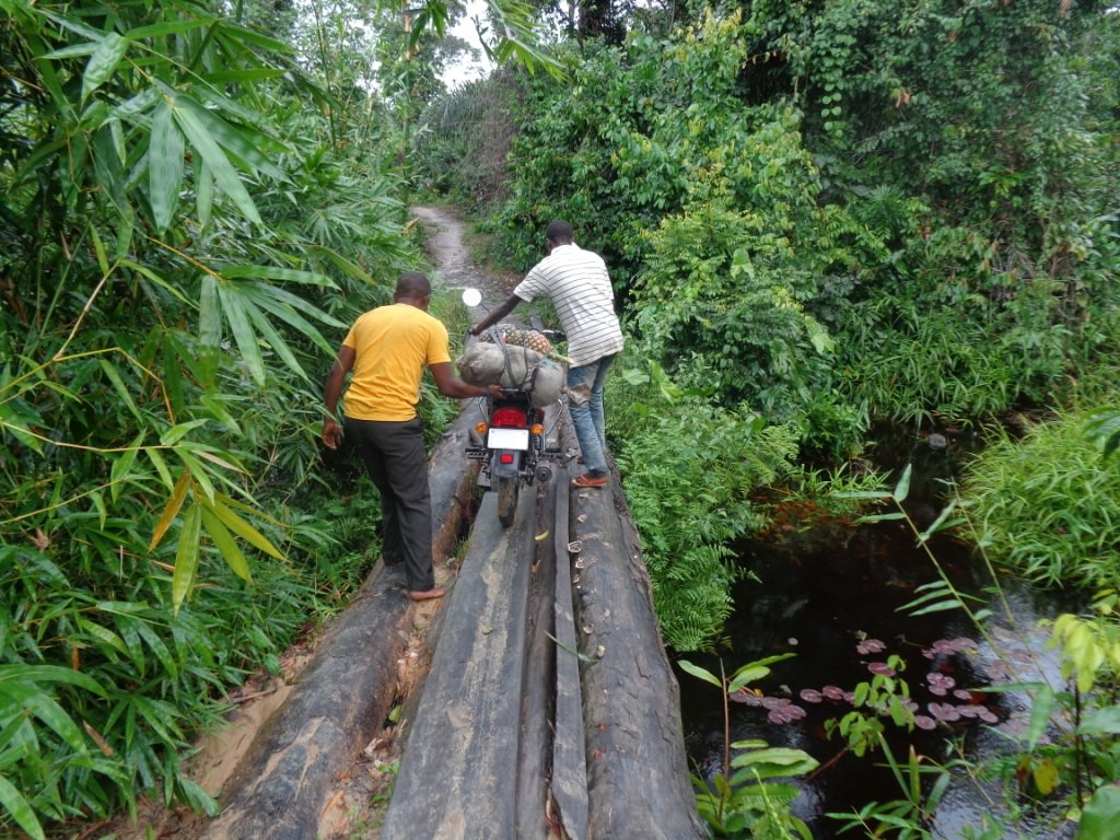 Alfred Zigbuo travels to various churches on a motorcycle. The team is walking the bike across a log bridge during a mission journey to Mutakuya Village, about 27 kilometers west of Kindu, Democratic Republic of Congo. Photo courtesy of Alfred Zigbuo