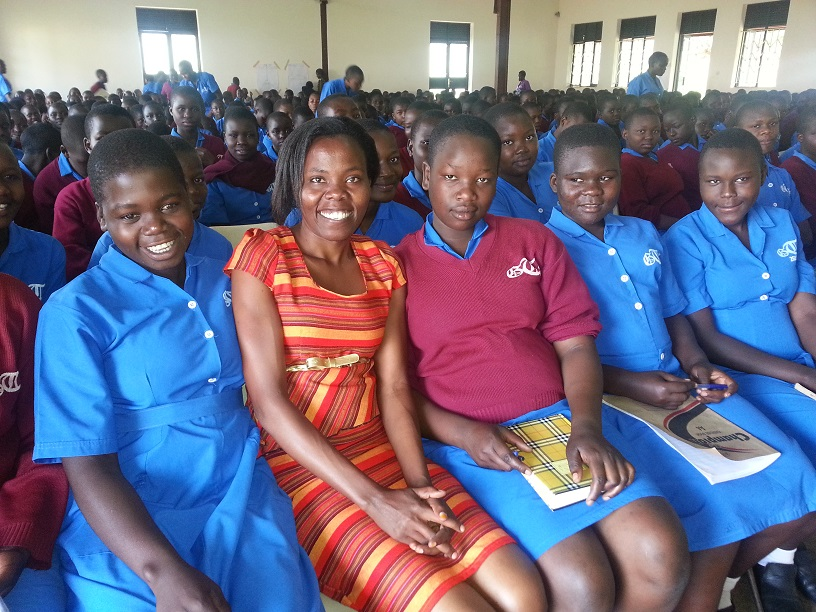 Lillian Achom spoke about technology careers at a career day at Tororo Girls School in Tororo, Uganda, near Kampala. Achom, in the orange dress, is an Africa University graduate. She works with Afchix to encourage girls and young women to take science and technology classes. Photo courtesy of Lillian Achom