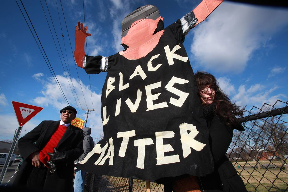 "Marie Campbell, assistant director of education at Scarritt-Bennett Center, holds a sign reading, ""Black Lives Matter."" Demonstrators gathered on Dec. 9 in Nashville to show their support for racial justice and immigration reform.  The man to the left is AME minister, Edward Thompson, with NOAH. (Nashville Organized for Action & Hope)."
