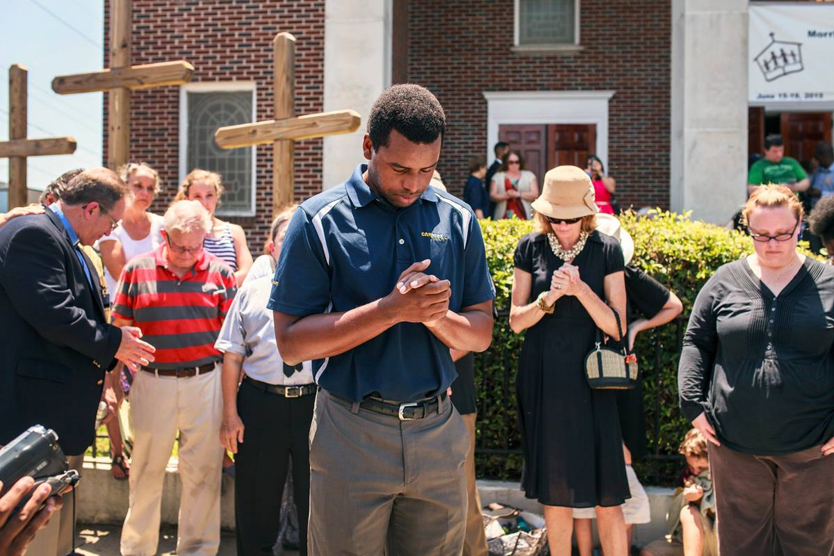 Robert Griggs (center) prays with others outside Morris Brown African Methodist Episcopal Church in Charleston, S.C. United Methodists joined AME members in prayer following the deadly shooting at Emanuel AME Church in Charleston. Photo by Lekisa Coleman-Smalls