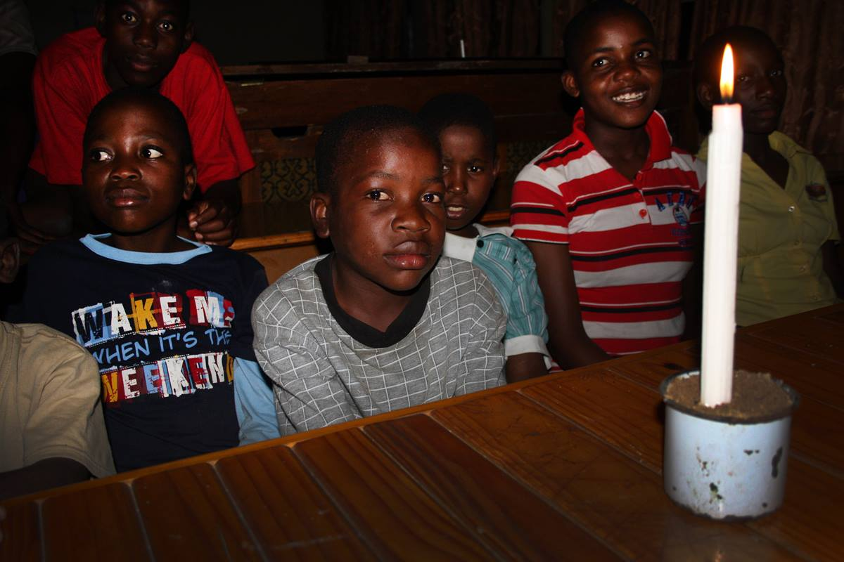 Boys at Home of Hope cluster around a candle during one of the frequent brownouts at The United Methodist Church's Nyadire Mission in Zimbabwe.
