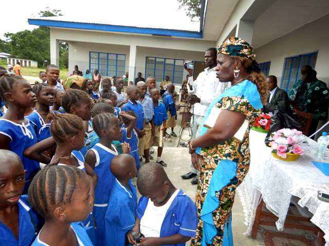 Marian Fofanah, head teacher of United Methodist Church Masorie, talks to pupils about taking care of the school.