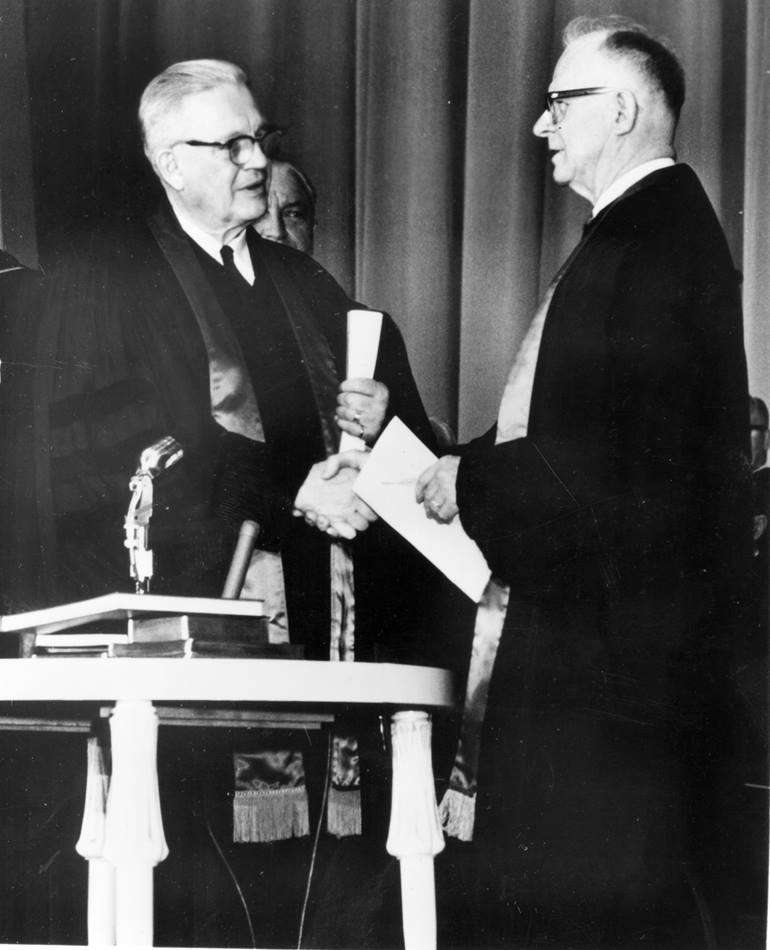 Evangelical United Brethren Church Bishop Reuben H. Mueller (left) and Methodist Bishop Lloyd C. Wicke join hands on April 23, 1968, symbolizing the merger between the two denominations.