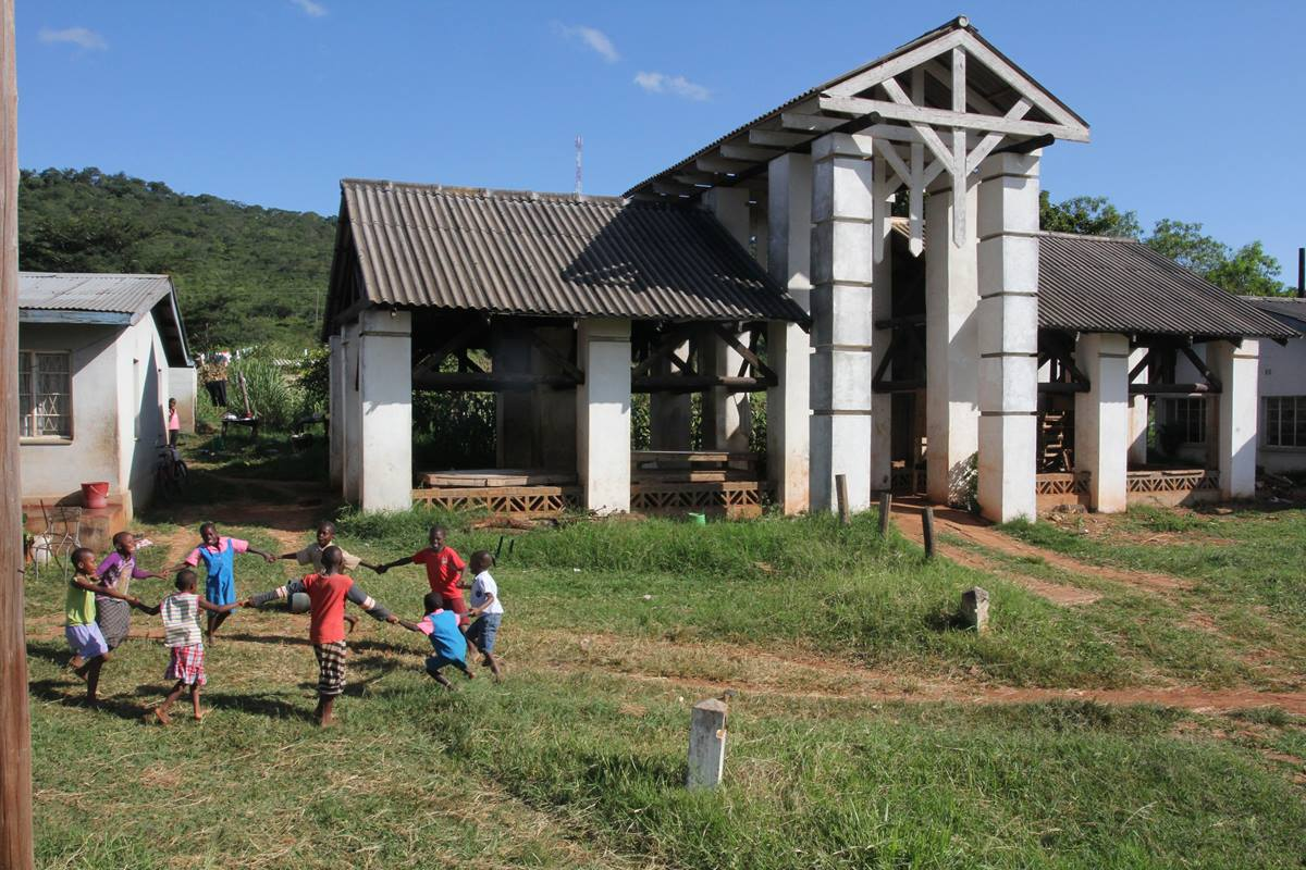 Children play a game in the farm area of Africa University, established by the 1988 United Methodist General Conference.  The building in the background was the original building where students gathered for breaks and outdoor dining in 1992.