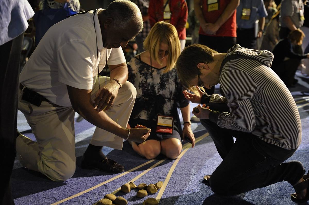 "Delegates pick up stones in the center aisle during an April 27 ""Act of Repentance toward Healing Relationships with Indigenous Peoples"" at the 2012 United Methodist General Conference in Tampa, Florida."