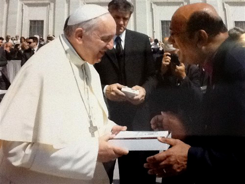 """United Methodist Bishop Sudarshana Devadhar presents copies of """"Celebrating God's Love"""" and the United Methodist Book of Worship to Pope Francis during an audience on May 13 in St. Peter's Square at the Vatican. The book includes an essay by the bishop. Photo courtesy of the Vatican."""