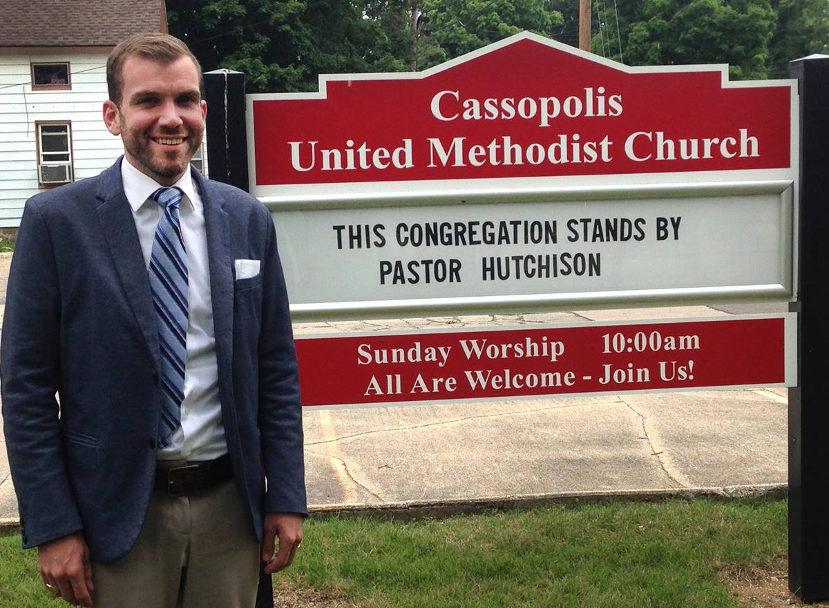 The Rev. Benjamin David Hutchison stands by the sign of Cassopolis United Methodist Church where he served as pastor for two and a half years. He recently was forced to resign from his post at the church against the congregation's wishes. Photo courtesy of Benjamin David Hutchison