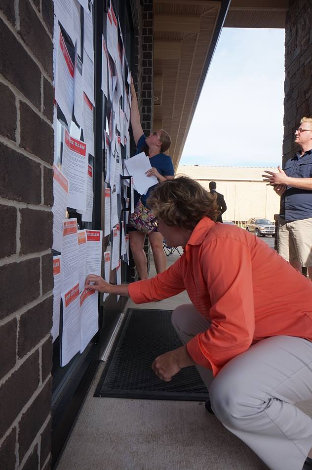 """United Methodists post petitions to the office door of Michigan Area Bishop Deborah Lieder Kiesey, urging the denomination to """"Stop the Harm"""" against lesbian, gay, bisexual, transgender and queer individuals. Photo courtesy of Reconciling Ministries Network"""