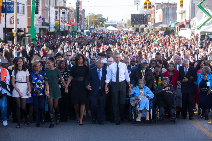 "The Obamas hold hands with Rep. John Lewis (D-Ga.) as they begin the march across the Edmund Pettus Bridge to commemorate the 50th anniversary of ""Bloody Sunday"" in Selma, Alabama, March 7, 2015.  Official White House photo by Lawrence Jackson."