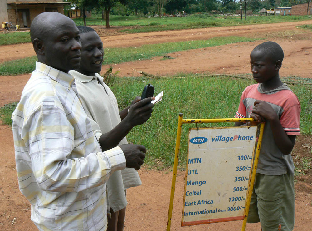 Men in Uganda use a mobile phone. Photo by Ken Banks, kiwanja.net.