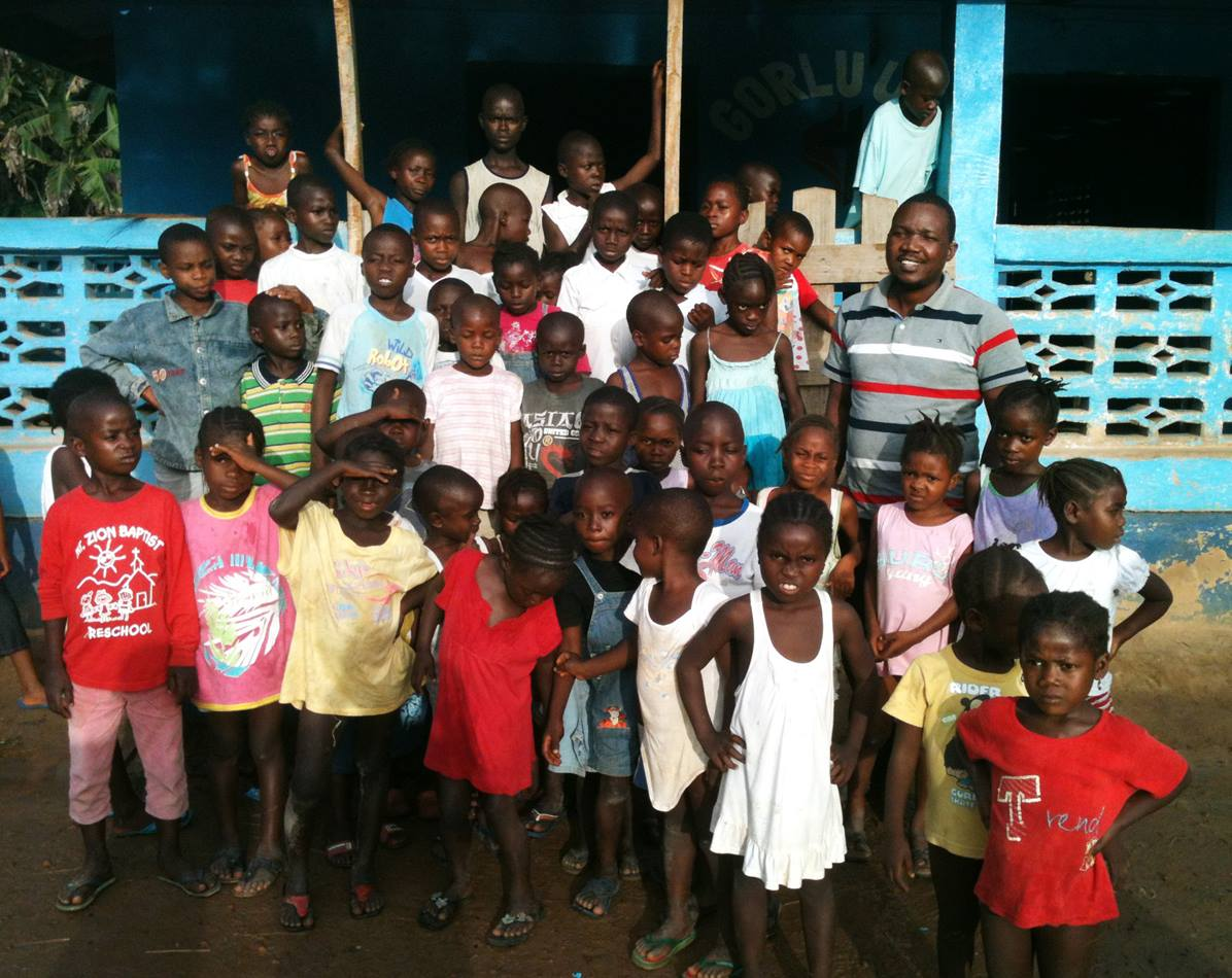 Jefferson Knight stands with a large group of children orphaned by Ebola. The children are living at the church's Gorlu Care Center in Liberia. Photo by Julu Swen, UMNS