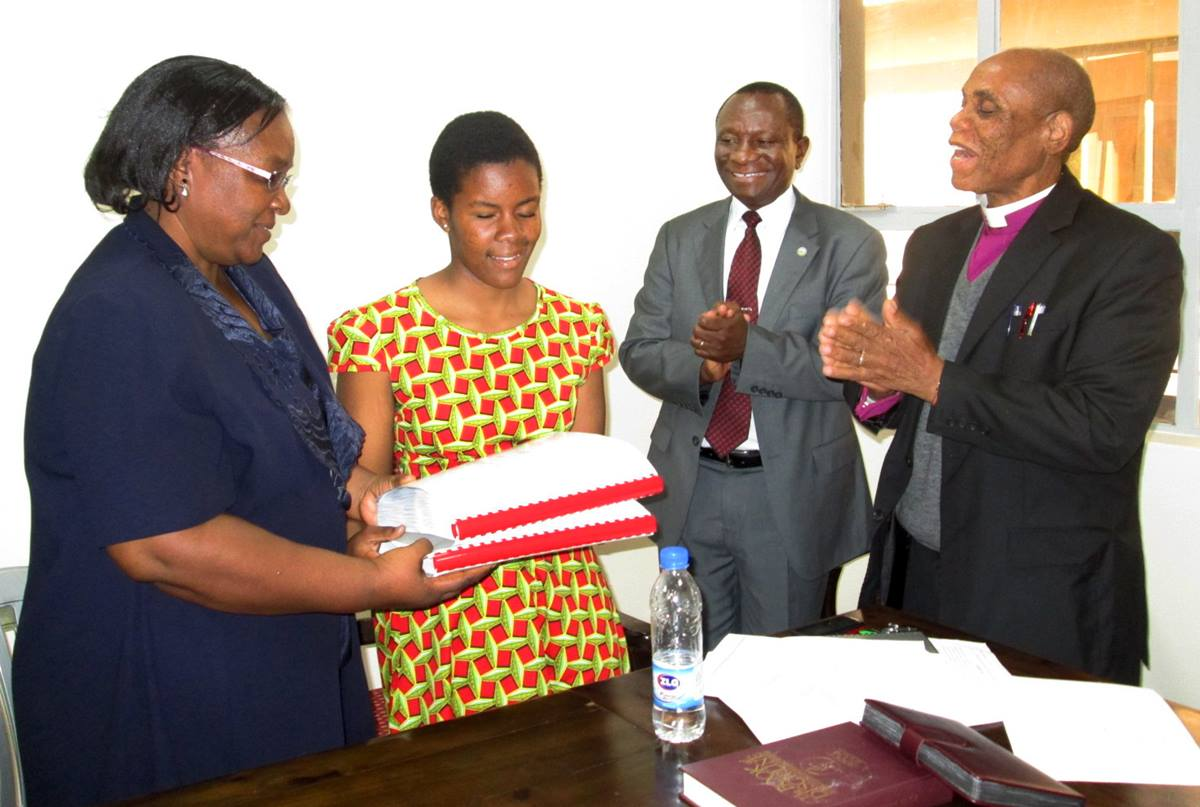 Laura and her mother receive a Braille hymnal in Shona from Bishop Eben Nhiwatiwa as the Rev.  Allan Gurupira looks on. Photo by Priscilla Muzerengwa, UMNS