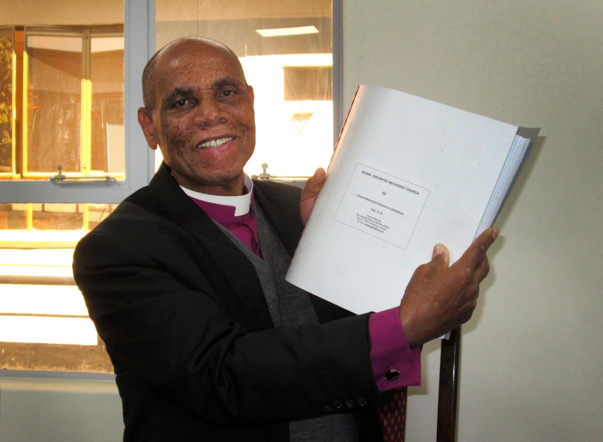 Bishop Eben Nhiwatiwa displays the new Braille Shona hymnal. Photo by Priscilla Muzerengwa, UMNS