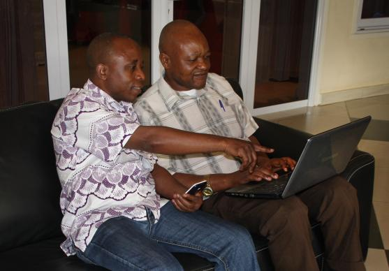 John Kaumba Makulu, left, and the Rev. Chris Tshitenga work together on a video about community health workers and a United Methodist Communications training in Kamina. Tshitenga plans to develop a radio story from the video. Photo by Vicki Brown, UMNS.